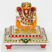 Marble ganesh idol sporting a turban and sitting on chowki